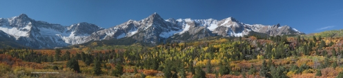 The Mount Sneffels Range is surrounded by golden aspen fall folage and has a new dusting of snow.
